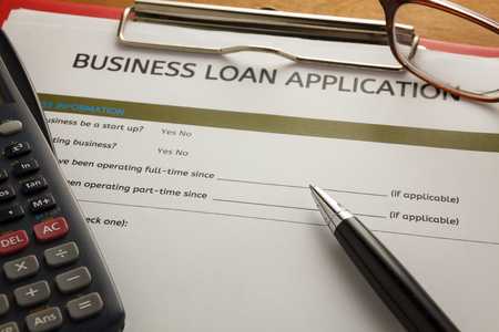 selective focus pen,Business loan application form,glasses ,calculator,red paper clip on wood background. Stock Photo