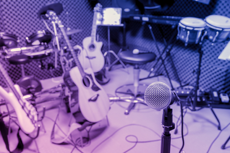 letras musicales: selective focus microphone and blur musical equipment guitar ,bass, drum piano, percussionist,lyric, background.