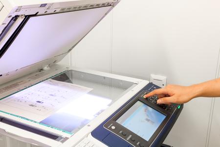 """fotocopiadora: alguien copia del documento en el texto de la copia machine.non-Ingl�s significa """"PRECAUCI�N No mire fijamente light.It puede causar incomodidad o irritaci�n en los ojos"""" Foto de archivo"""