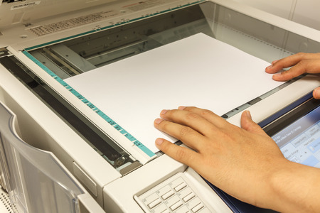 fotocopiadora: someone copy document at copy machine.non-English text mean CAUTION Do not stare at light.It may cause discomfort or irritation to your eyes,