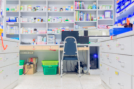 drug store: blur background drug shelves with PC computer in drug store. Stock Photo