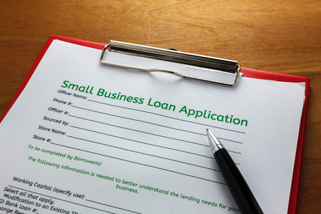 business loans: pen,small business load application on clip board.Clip board on wood table.