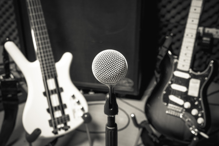 shure: selective focus microphone and blur musical equipment electric guitar ,bass,loudspeaker background.