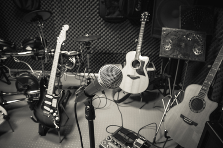 music band: selective focus microphone and blur musical equipment guitar ,lyric, drum piano background.