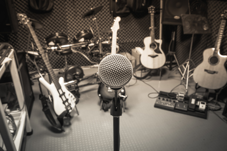 retro music: selective focus microphone and blur musical equipment guitar ,lyric, drum piano background.