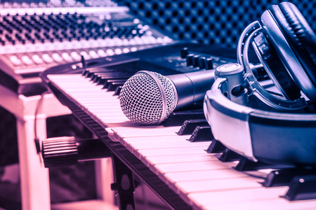 sound mixer: microphone,headphone on piano background.Blurred sound mixer.