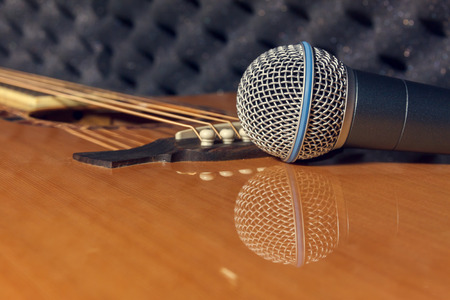 shure: selective focus pin of classic guitar in home recording studio.Microphone on classic guitar background. Stock Photo