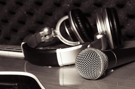 personas escuchando: micrófono, salida de auriculares en el fondo clásico de la guitarra en el estudio de grabación en casa. Foto de archivo