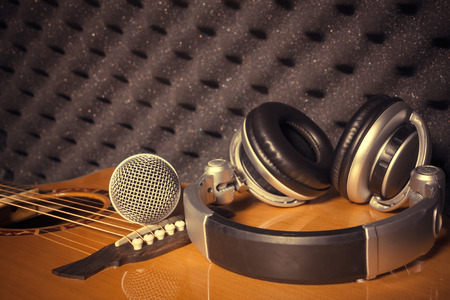 shure: microphone,headphone on classic guitar  background in home recording studio.