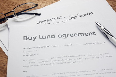 en,eyeglasses and land contract form on wood background.Bussiness buy and sell home concept. 免版税图像