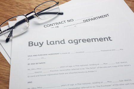 PenEyeglasses And Land Contract Form On Wood BackgroundBussiness