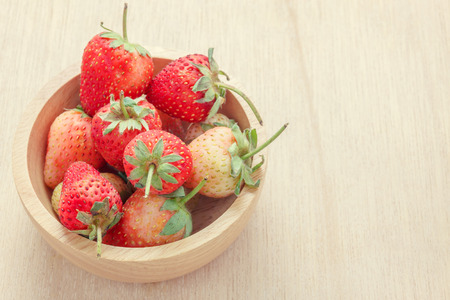 addle: selective focus fresh strawberry in wood bowl.wood bowl on wood background. Stock Photo