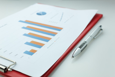 business background grown up concept the pen,business chart document and red clip board on white background.