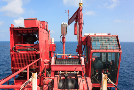 Crane offshore of offshore oil and gas field on remote wellhead platform with beautiful blue sky.