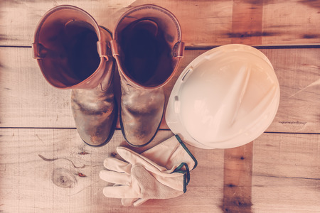 personal protective equipment: Top view the Safety boots.Gloves.White helmet.All personal protective equipment on wood background.