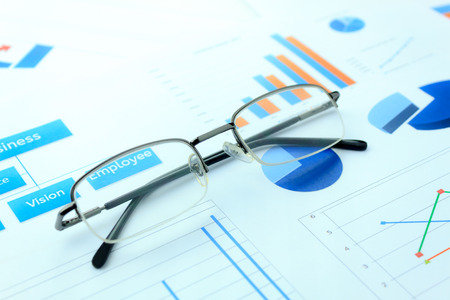 grown up: business background grown up concept the eyeglasses  on business chart document background. Stock Photo