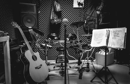 Selectieve focus de microfoon en muzikale instument de gitaar, de teksten, de drum, de bas, de luidsprekers, de achtergrond van de koptelefoon. Muziek productie band concept. Stockfoto