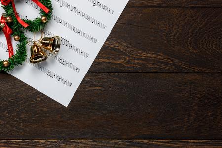 Vista superior de papel de nota musical de Navidad con la guirnalda de la Navidad en el fondo de madera y de la copia.