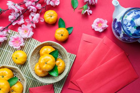 Draufsichtzubehör chinesische Festivaldekorationen des neuen Jahres orange, Blatt, hölzerner Korb, rotes Paket, Pflaumenblüte, Teekanne auf rotem Hintergrund.