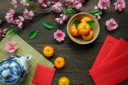Top view accessories Chinese new year festival decorations.orange,leaf,wood basket,red packet,plum blossom,teapot on wooden table background.