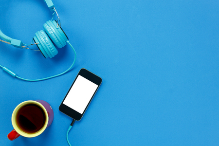 Top view black coffee,mobile phone and headphones on blue background with copy space.