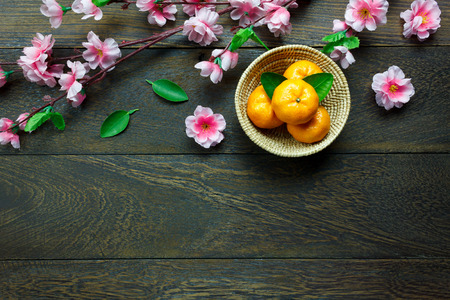 Top view orange,leaf,wood basket,plum blossom on table wooden background with copy space.