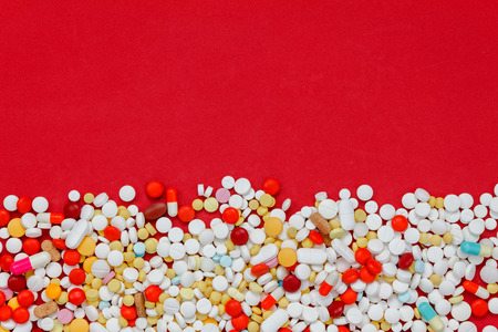 Top view colorful medicine on red background.