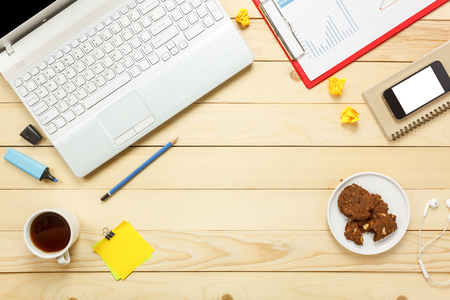 Top view laptop notebook,pencil,black coffee,charted paper,stationary,earphones,cookies on office desk background.