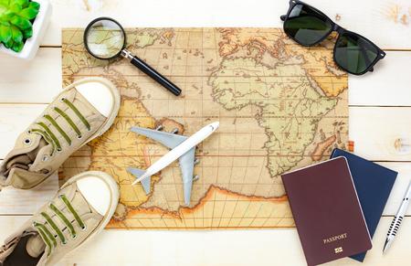 Artículos esenciales del recorrido de la visión superior Las gafas de sol del zapato del aeroplano del pasaporte del mapa del árbol del cuaderno en el fondo de madera blanco.