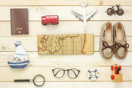 Top view essential travel summer items.The woman shoes notebook map passport airplane boat music eyeglasses on white  wooden background.