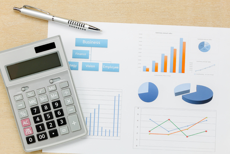 Top view business summary of the year and pen, chart calculator on wood  office desk background. Stock Photo