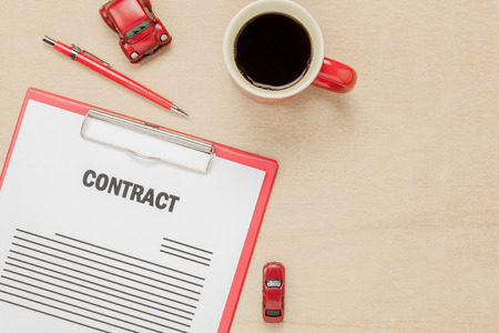 property management: Top view business contract form with coffee  car pen with  on wooden background. Stock Photo