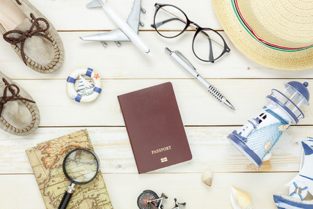 Top view accessories to travel beach.The woman shoes notebook map passport airplane boat music eyeglasses on white  wooden background. Stock Photo