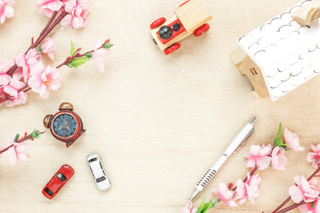 Top view business office desk concept. Wood house  also car and clock on wooden shelf.The beautiful pink flower with pen on wood background with copy space.