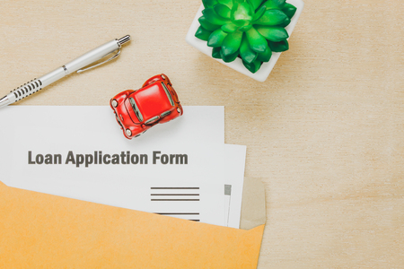 financial item: Top view business office desk background.The business loan appcation form pencil  letter and car tree on wooden table background with copy space.