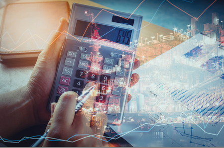 Double exposure technical finance and offshore oil and gas platform in night time background concept.hand man calculate finances and saving economy on charted and notebook on business office desk. 免版税图像