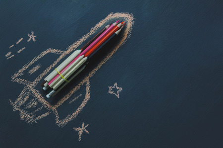 Top view rocket fling on the space with star.Crated by colorful pencil and drawing by chalk board on backboard or table.Start up business.Back to school and education concept.flat lay.copy space. Stock Photo