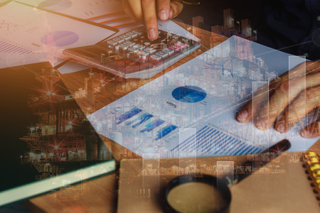 close up asian man calculate banking finance or saving economy background.Double exposure industrial offshore oil and gas platform for cost and growth up business on table office desk with accessories