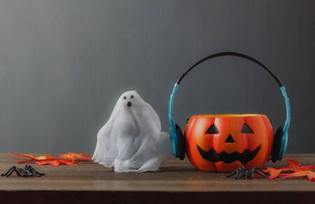 audio mixer: Happy Halloween festival decorations and music concept.Mix different of accessories on modern rustic brown wooden at home office desk.Blur grudge grey wallpaper background after object and copy space