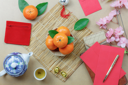 Top view shot of arrangement decoration Chinese new year & lunar festival concept background.Orange & tea pot also red pocket money with map to travel.Variety object on modern brown wood at home desk. 版權商用圖片