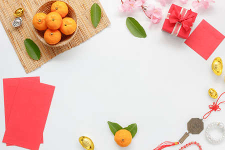 Top view shot of arrangement decoration Chinese new year & lunar festival concept background.Orange & tea pot also red pocket money with map to travel.Variety object on modern brown wood at home desk. Stockfoto
