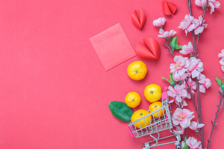Table top view of arrangement decoration Chinese new year & lunar holiday background concept.Orange in shopping cart or trolley with accessories on modern red wood wallpaper.Idea shopping in season.