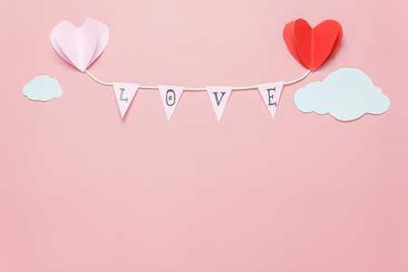 Flat lay image of decoration valentines day background concept.Text sign of season with paper cut balloon love hang on beautiful pink sky with cloud.Several objects on pink wallpaper.pastel tone. Stock Photo
