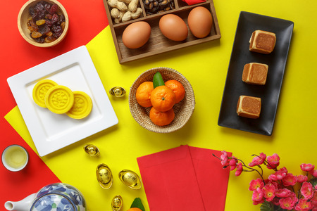 Table top view aerial image of accessories and Chinese new year and Lunar new year festival concept background.Mix variety object for the season.Difference items on modern red & yellow.pastel tone.