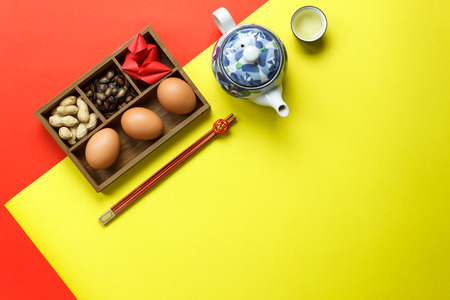 Above view of accessories Lunar & Chinese New Year holiday background concept.Free space for mock up & template design.Difference objects on modern rustic red & yellow paper at table.pastel tone.