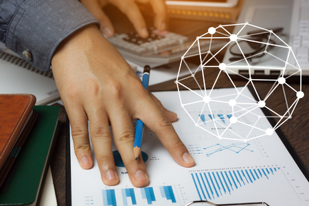 Double exposure world network system with finance & savings economy concept.Close up business man working on modern brown office desk about calculate cost form graph sheet document with calculator.