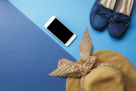 Mobile phone with many essential items hat and shoes on modern rustic duo blue paper with space creative design.