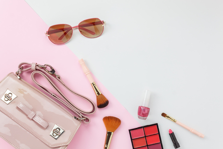 Table top view accessory of clothing women  plan to travel in holiday background concept.Hand bag with many essential  items cosmetic and sun glasses on modern white & pink paper.Duo with pastel tone.