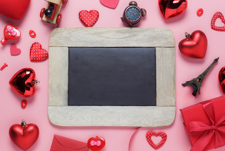 Table top view aerial image of decoration valentines day background concept.Flat lay arrangement of blank space blackboard & essential items on modern rustic pink paper for mock up creative design