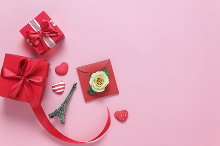Table top view image of decoration valentines day background concept.Flat lay white rose and essential symbol love season with several objects on modern rustic pink paper.pastel tone creative design. Stock Photo